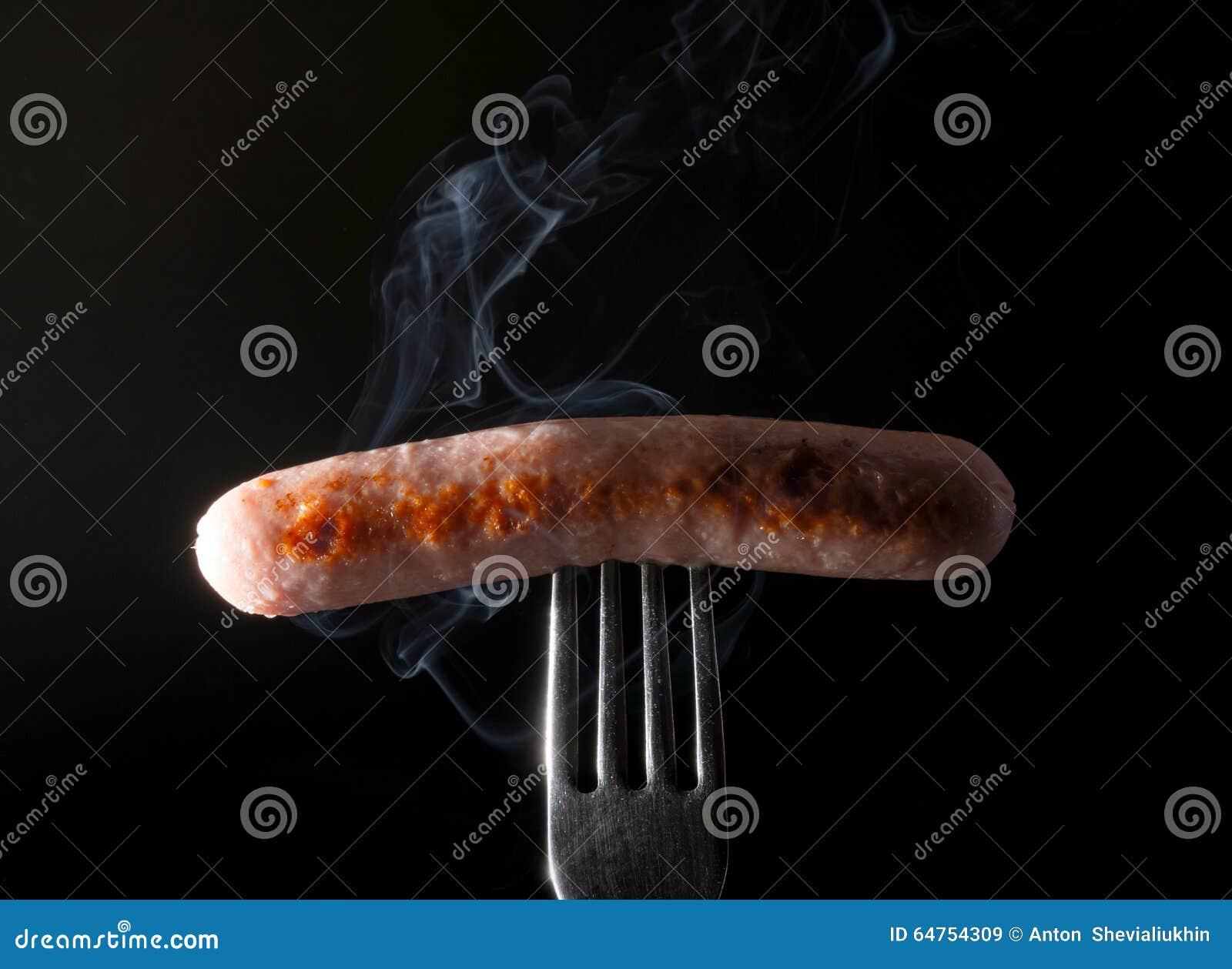 Grillad korv på en gaffel som ångar bakgrund för röksvart