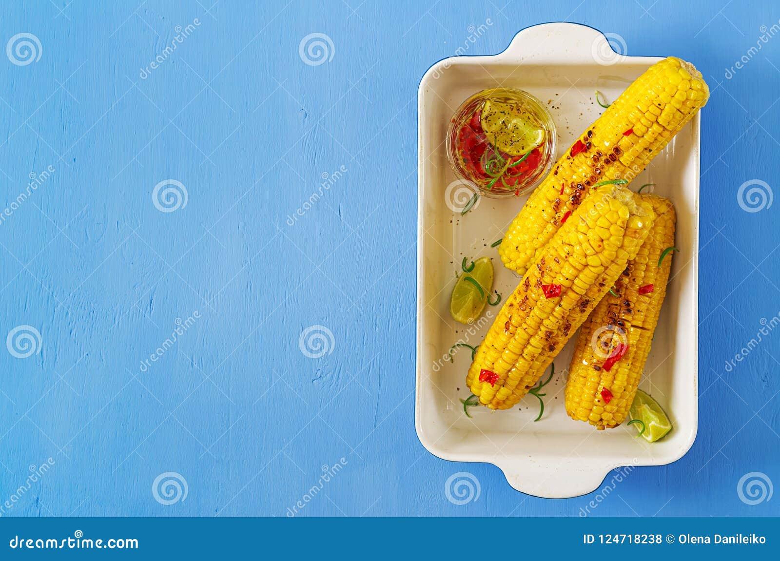Grillad majs med mexikansk sås, chili och limefrukt på blå bakgrund