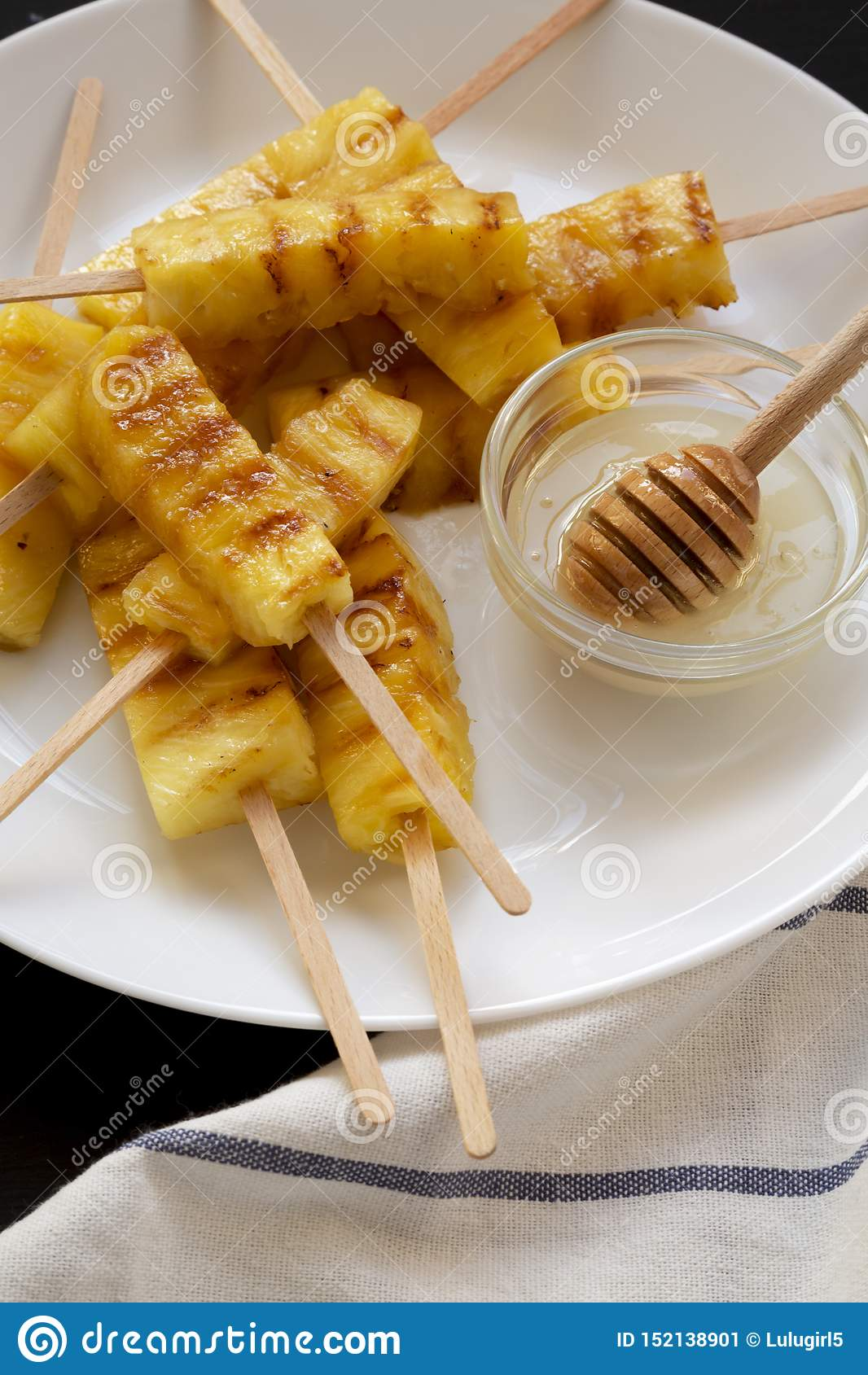 Grillade ananaskilar på en vit platta på en svart yttersida, sikt för låg vinkel Sommarmat N?rbild