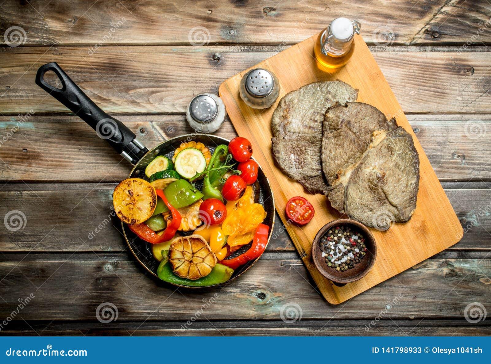 Grillade grönsaker i en panna med stekte nötköttbiffar
