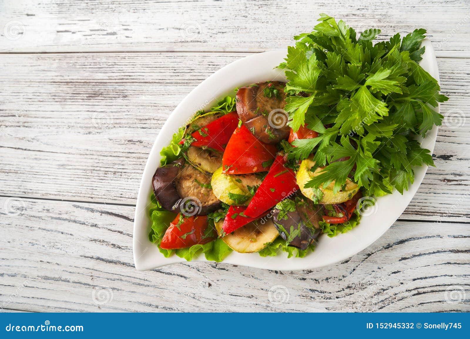 Grillade grönsaker i en vit plattanärbild Mellanmål från bakade grönsaker med Provencal örter som kopierar utrymme