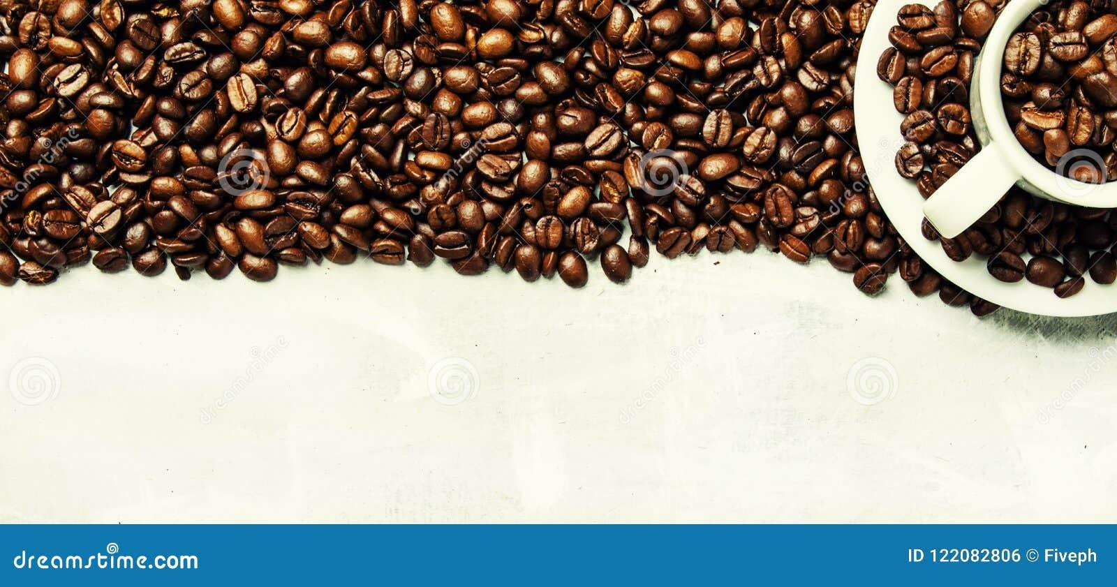 Grillade kaffebönor i en vitt kopp och tefat, grå matbackgr