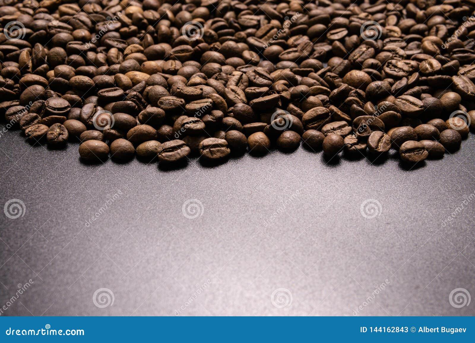 Grillade kaffeb?nor i massa p? en svart bakgrund shoppar den m?rka cofeen grillade kaf?t f?r kornanstrykningarom, naturlig coffe