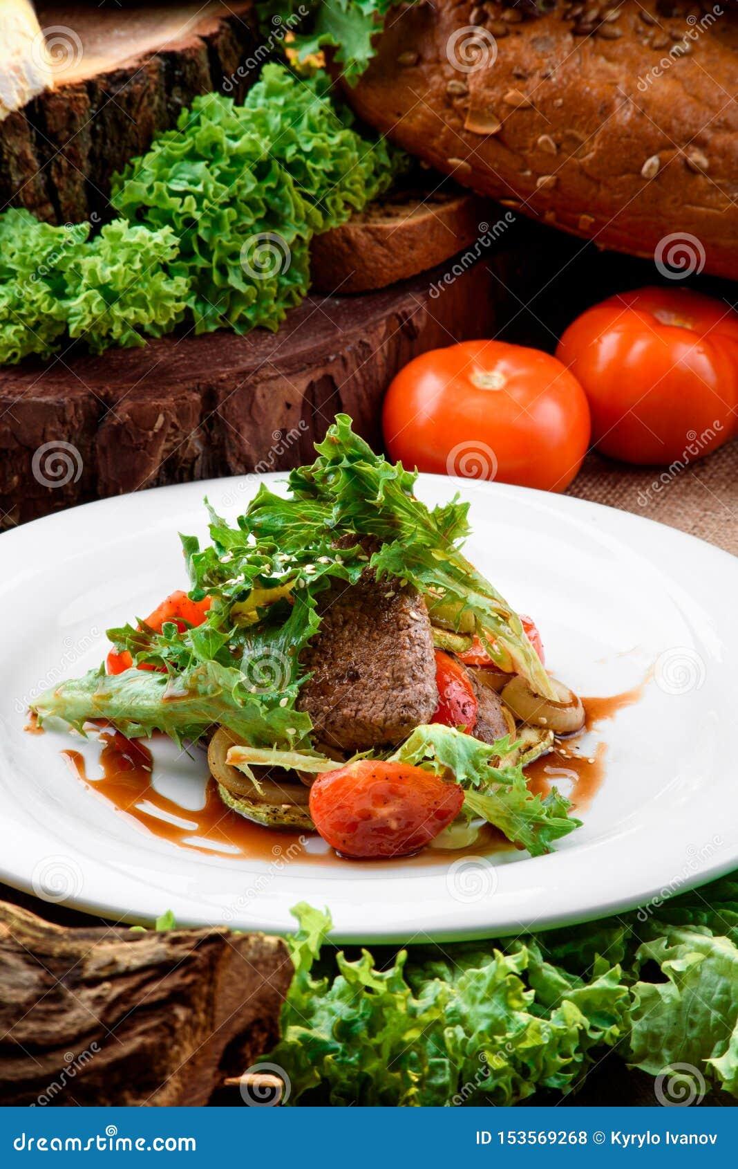 Grillat kött med grillade grönsaker och ny grönsallat i teriyakisås på den vita plattan på mörk träbakgrund