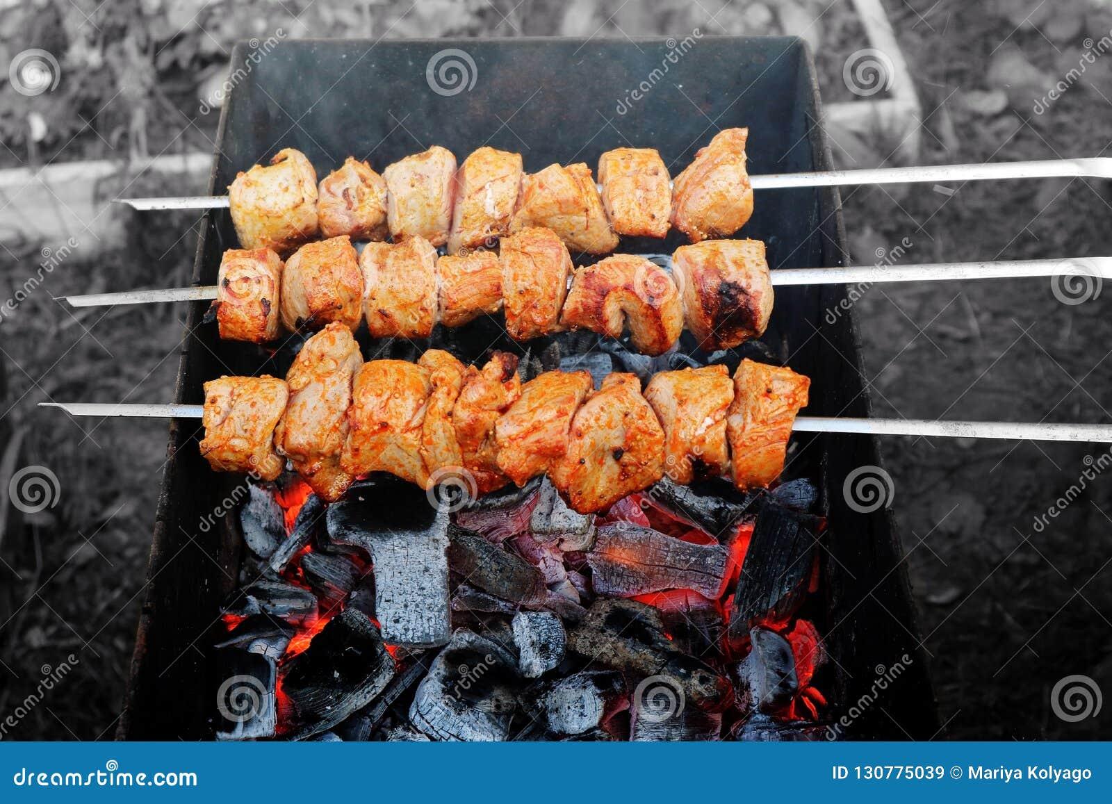 Grillat kött på steknålar över branden