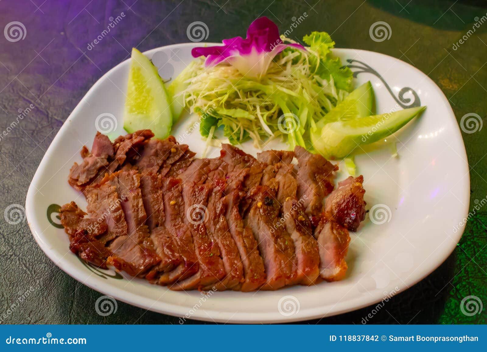 Grillat nötkött på en vit platta med såsen och grönsakerna