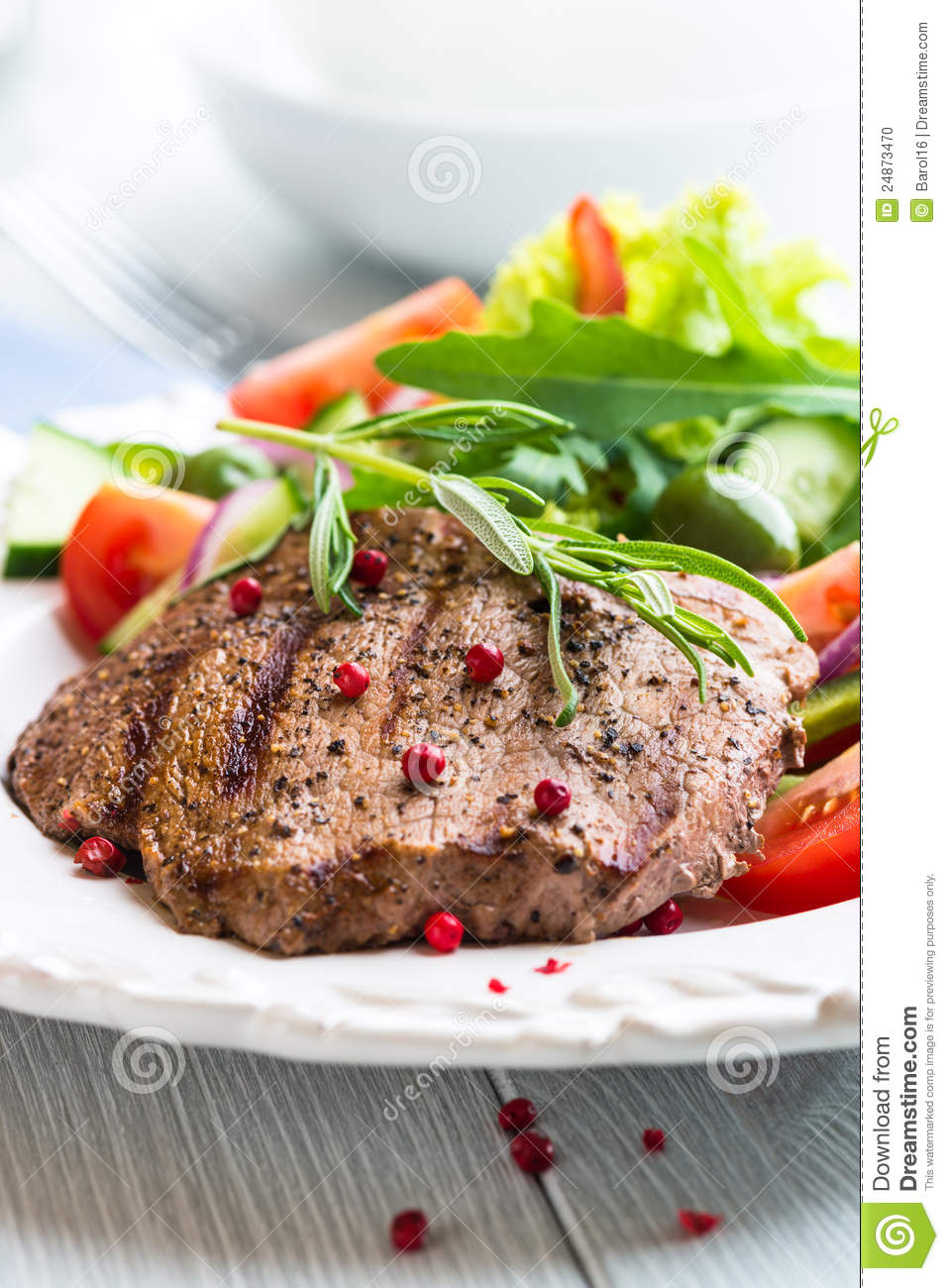 Grilled beefsteak with vegetable salad; flavored with rosemary and ...