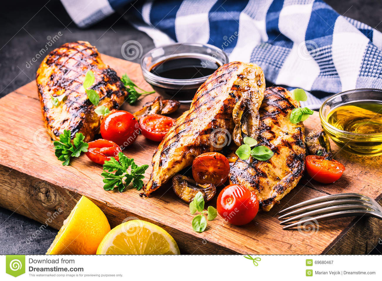 Grilled chicken breast in different variations with cherry tomatoes, mushrooms, herbs, cut lemon on a wooden board or teflon pan.