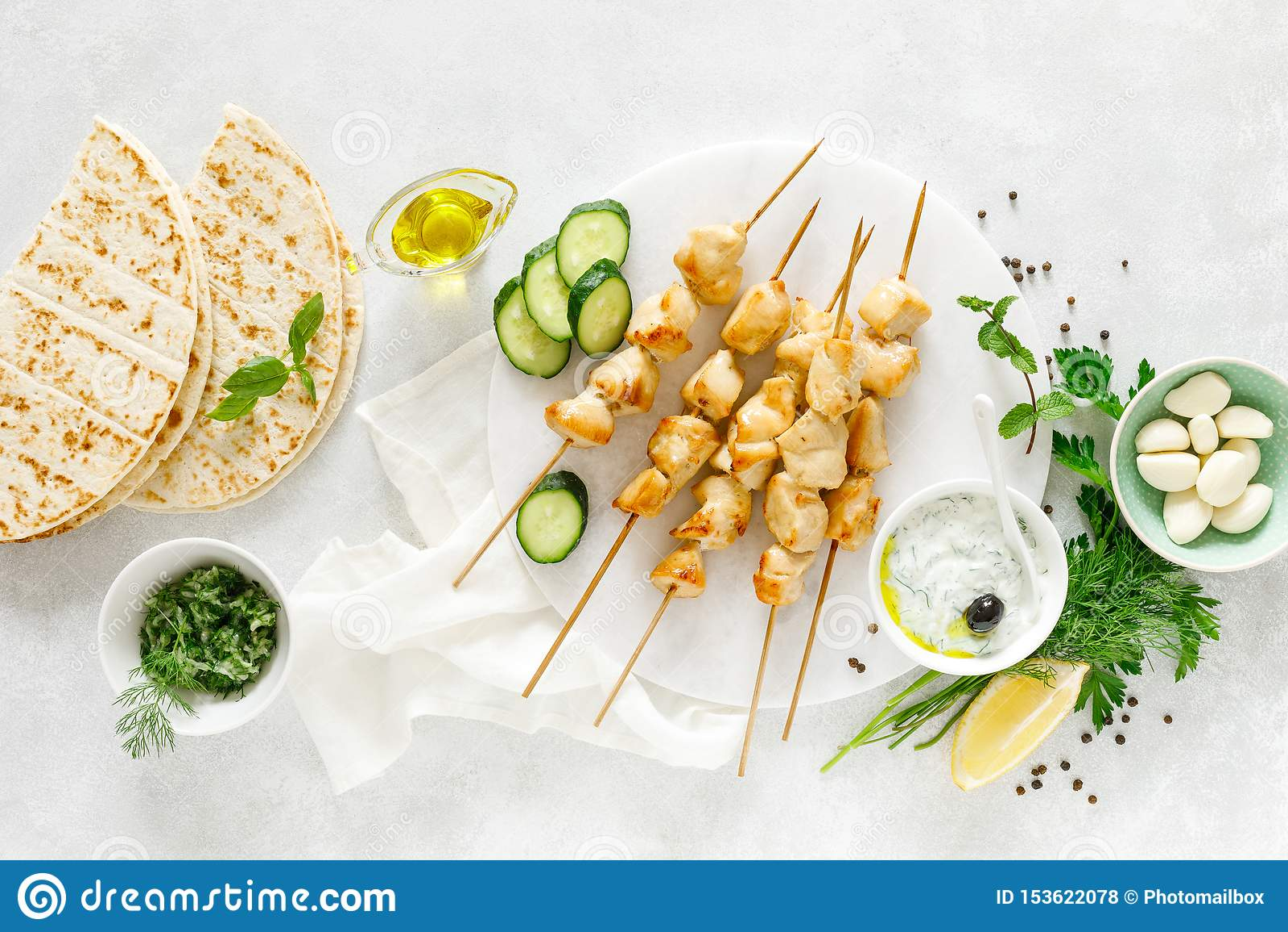 Grilled chicken kebab on skewers and traditional Greek tzatziki yogurt sauce