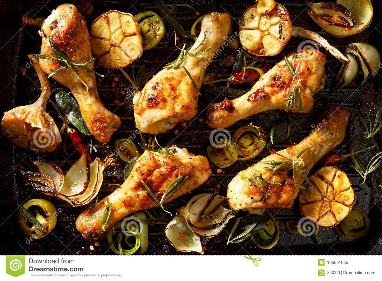 Grilled chicken legs with addition of aromatic rosemary, garlic, onion, leek and spices on a grill plate