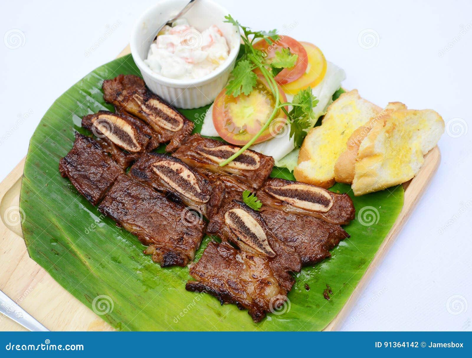Grilled desbastou reforços de carne de porco com pão e os tomates na banana folheiam