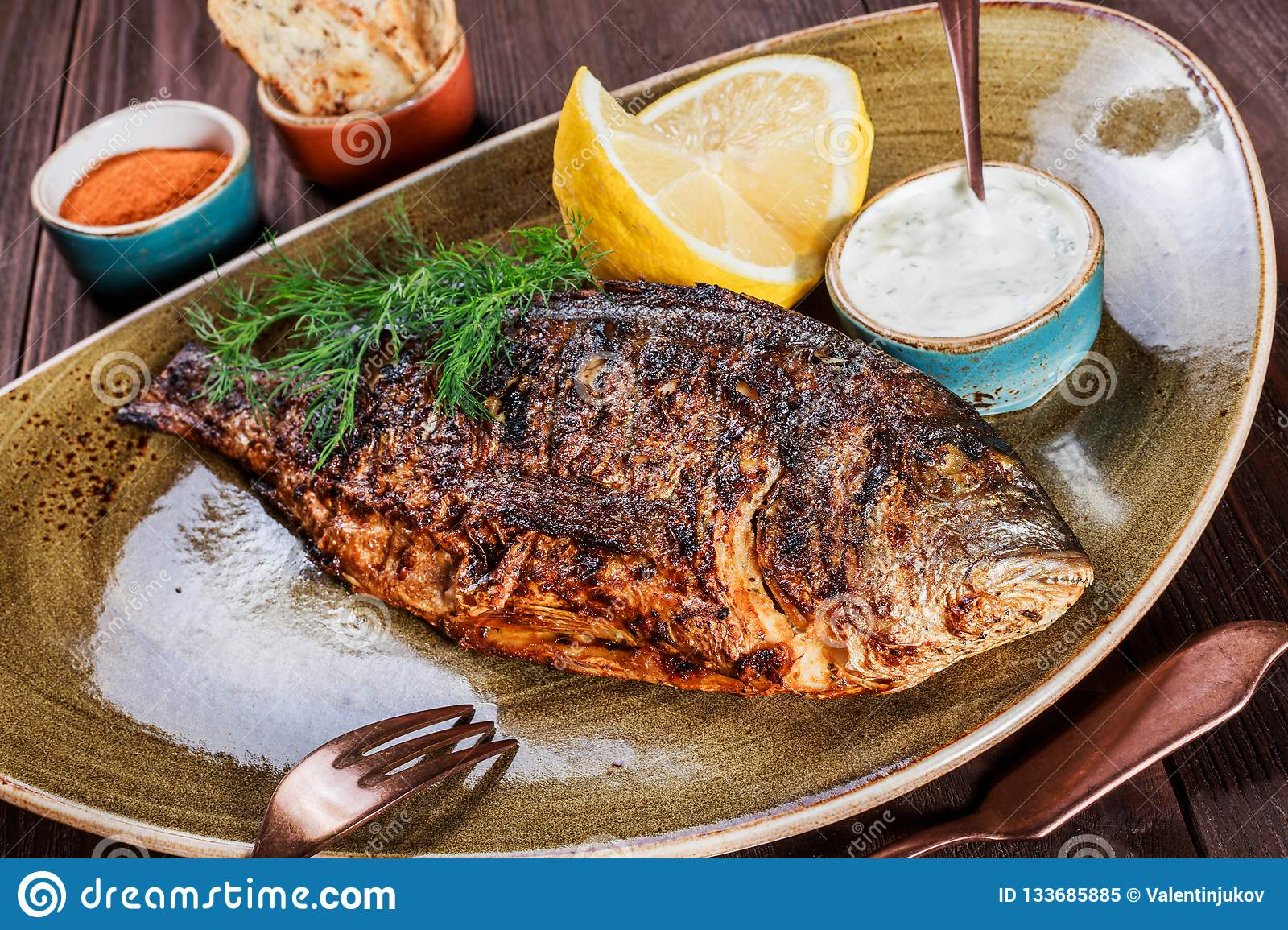Grilled dorado fish with lemon and greens on plate on wooden background.
