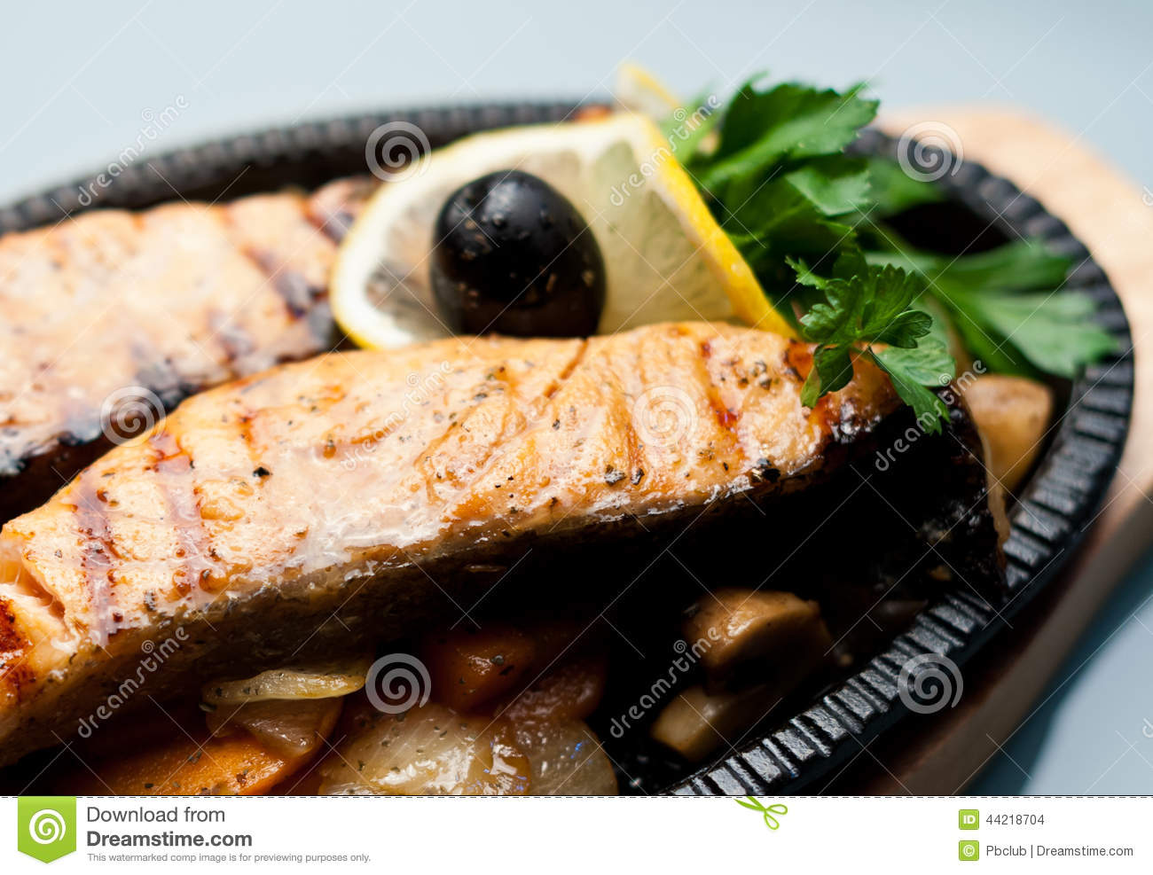 Grilled fish steaks on a bed of vegetables garnished with parsley.