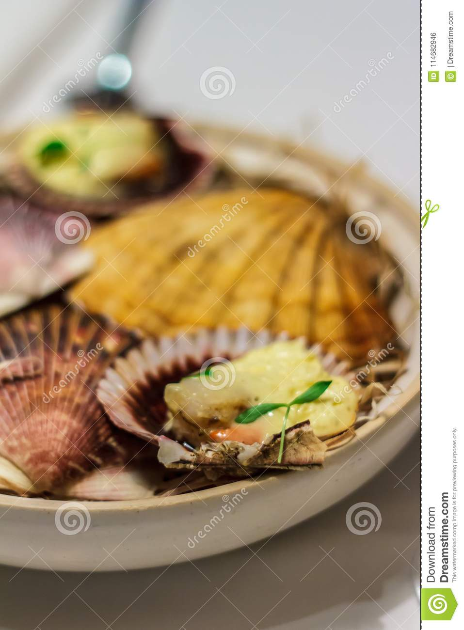 Grilled Fresh Scallop on Shell and lemon on the plate side view