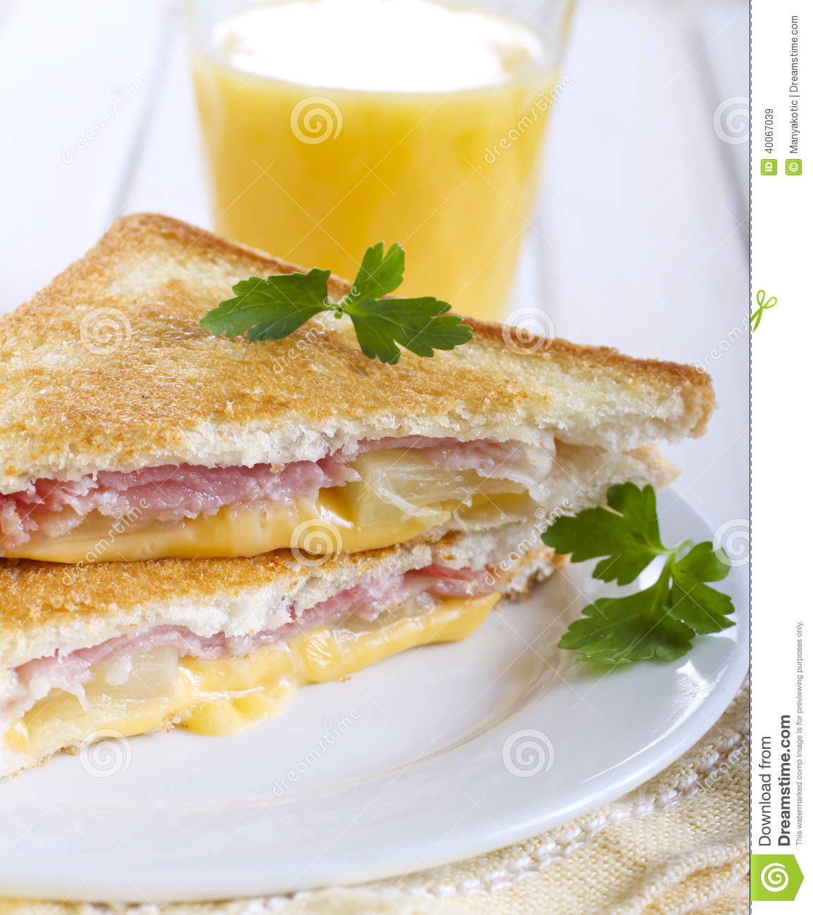 Grilled ham, pineapple and cheese sandwich and glass of orange juice.