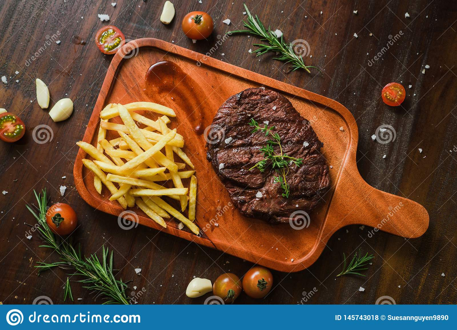 Grilled kebab grilled meat steak lies with french frieson a Rustic old elegant wooden cutlery cutting chopping board chili, with t