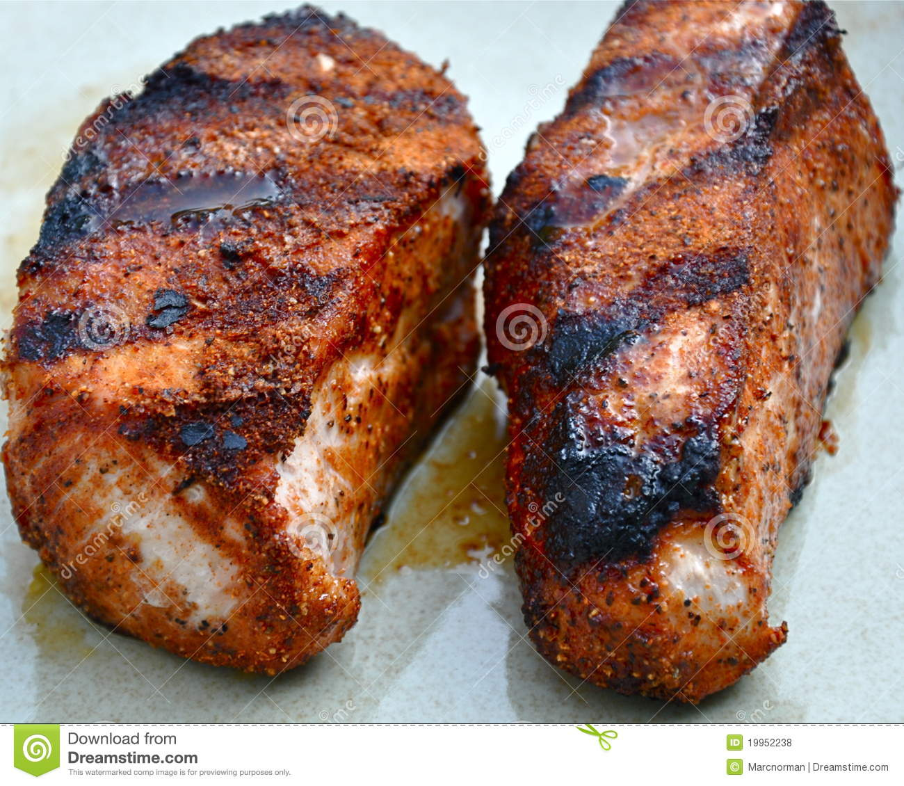 Juicy pork chops fresh off the grill. Focus near top-front, with ...