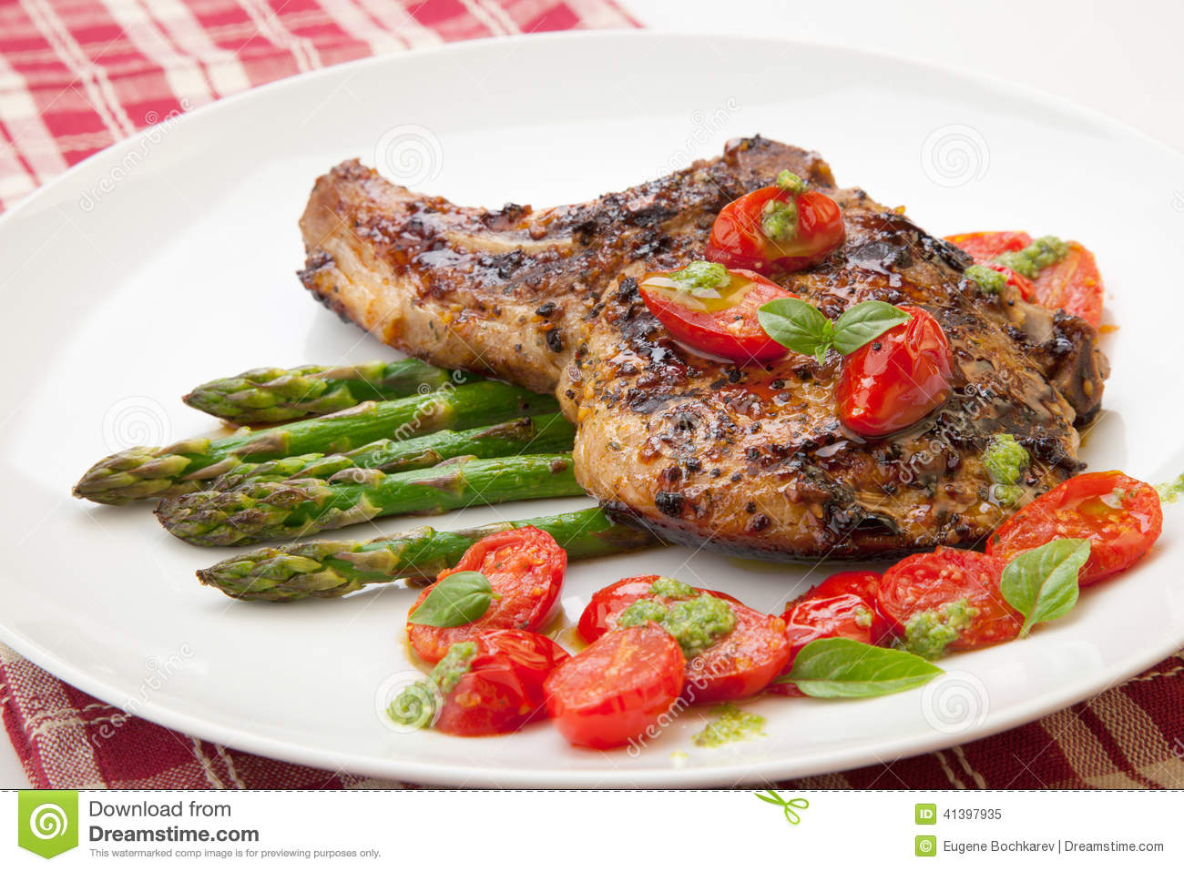 Grilled pork chops and asparagus. Served with fried grape tomatoes ...