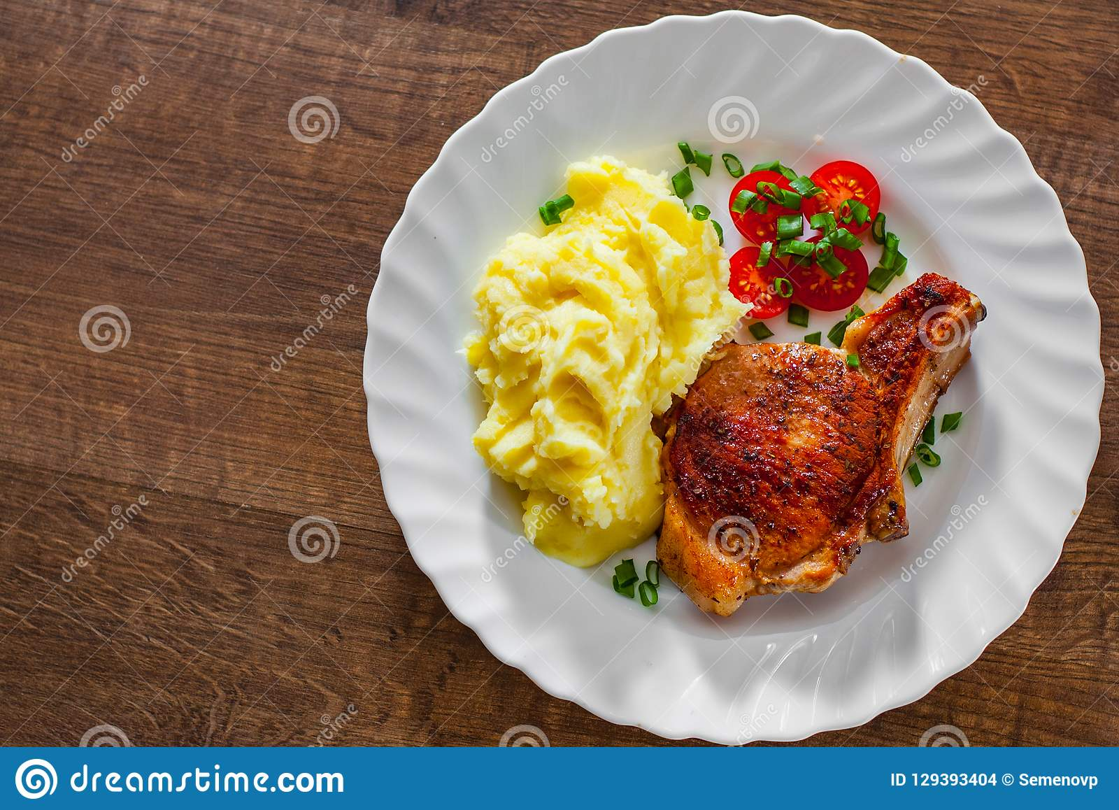 Grilled pork loin with mashed potatoes and salad in white plate on wooden table background with copy space. top view