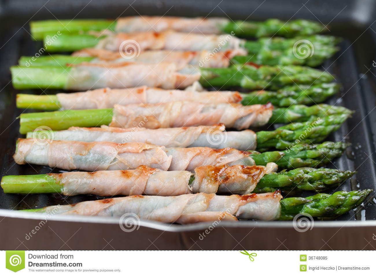 Prosciutto wrapped green asparagus on a grilling pan.