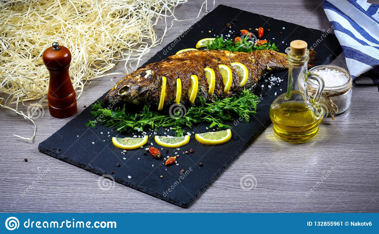 Grilled river fish on a plate with lemon and baked vegetables and parsley. Food recipe photo, copy text