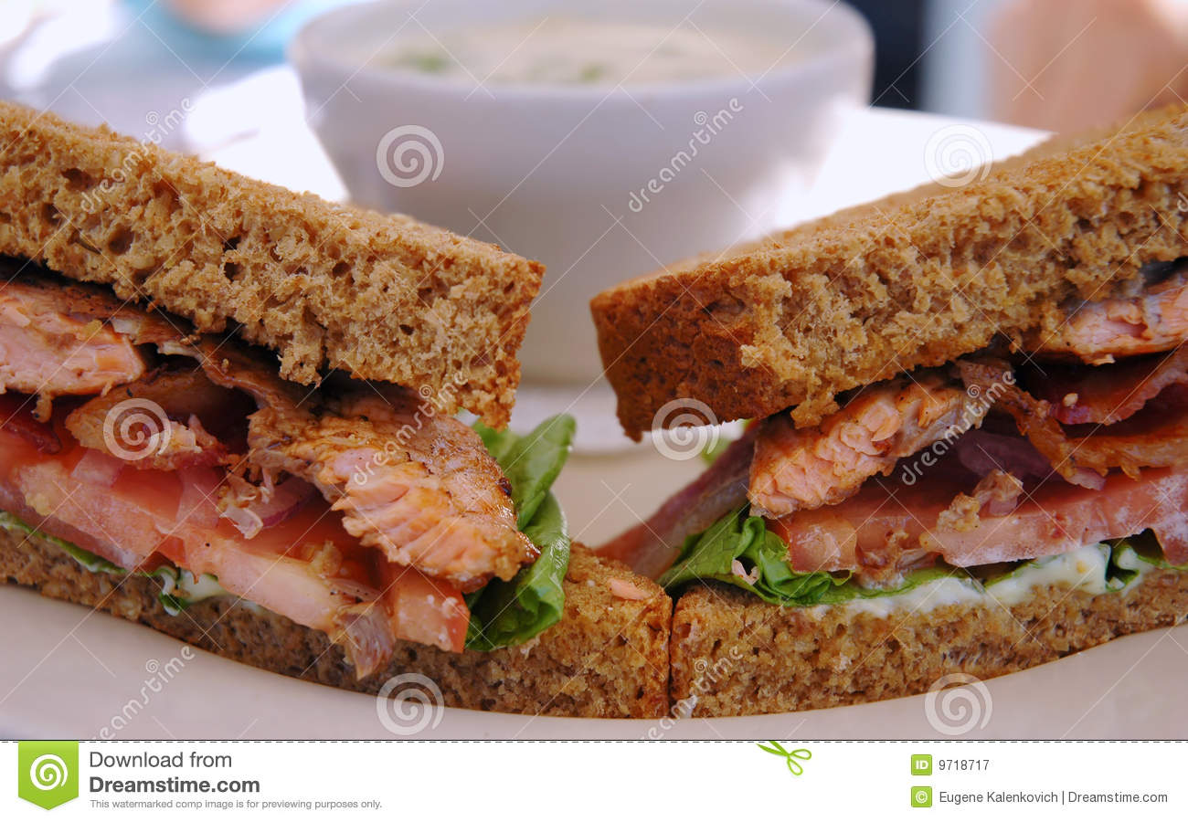 plate with grilled salmon sandwich on pumpernickel bread and a cup ...