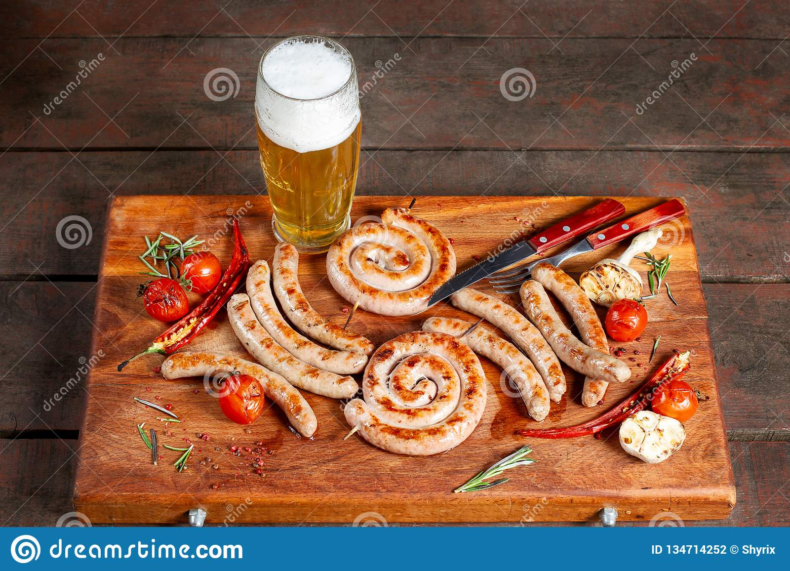 Grilled sausage ring on wooden board. Beautiful composition laid out on the board of natural wood.