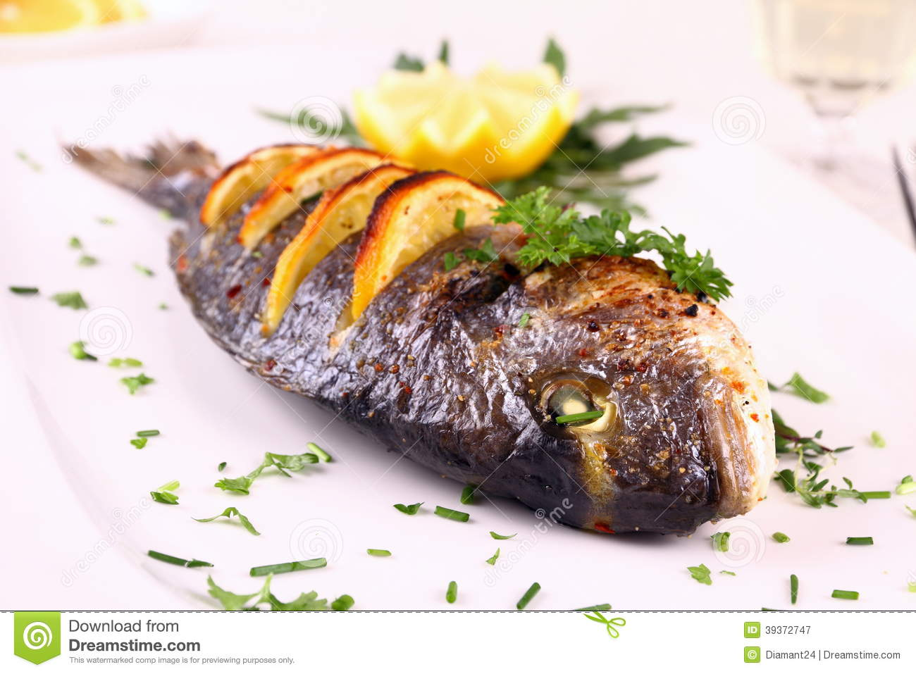 Grilled Sea Bream Fish, Lemon, Arugula On White Plate Stock Photo ...