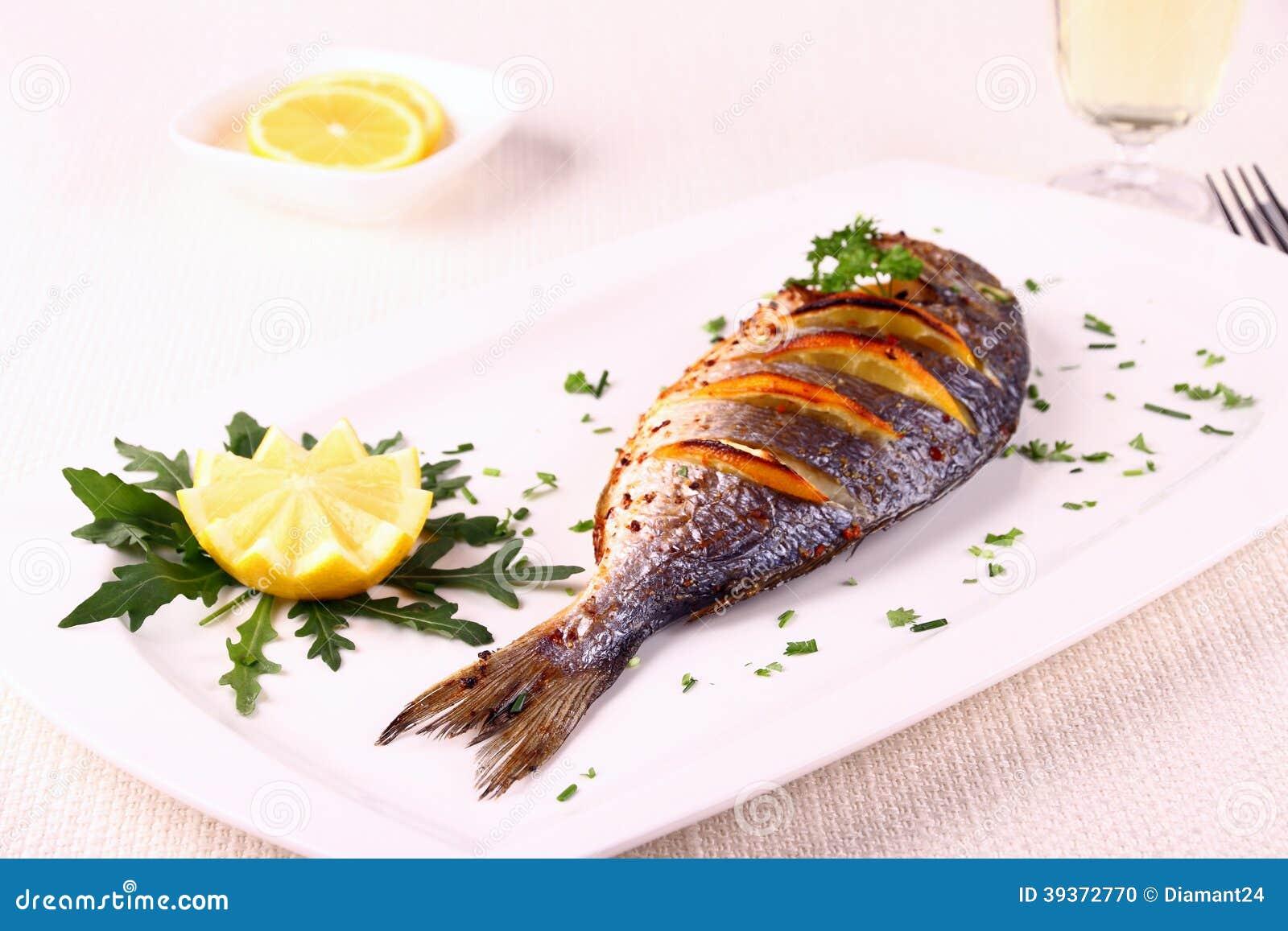 Grilled sea bream fish lemon arugula on white plate for Sea salt fish grill