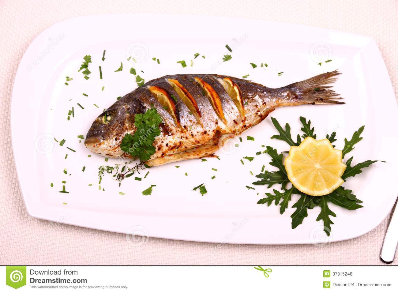 Grilled sea bream fish lemon arugula on white plate for Best white fish to eat