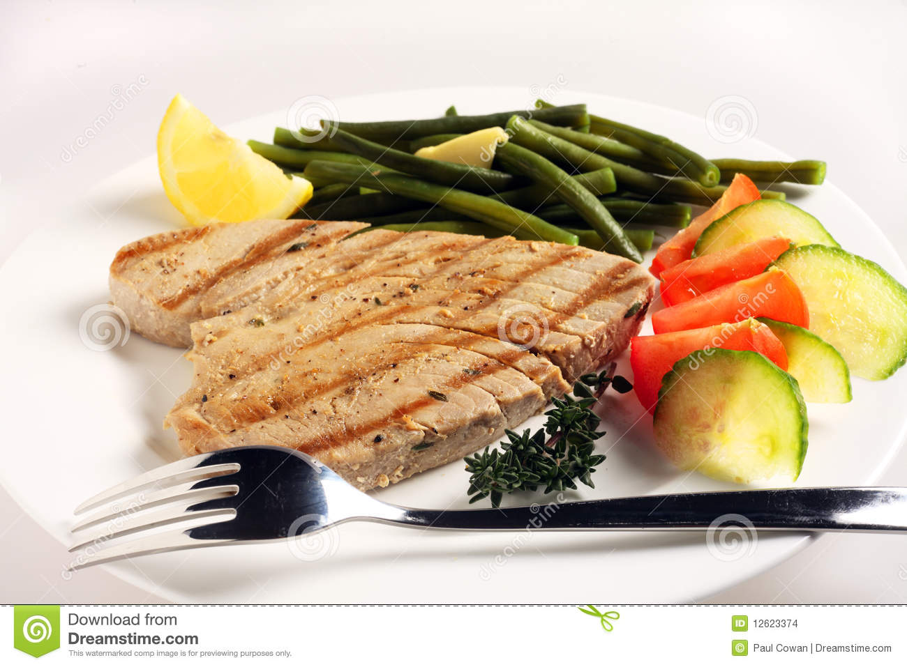 meal of grilled tuna steak with a salad of tomato and cucumber and ...