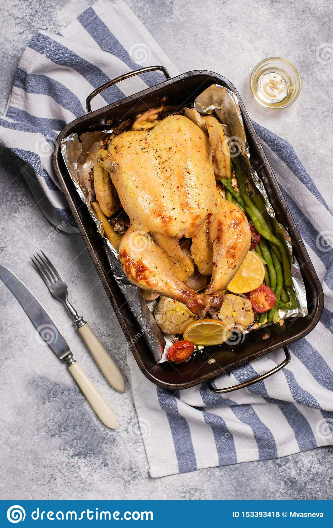 Grilled whole chicken with vegetable in dripping pan