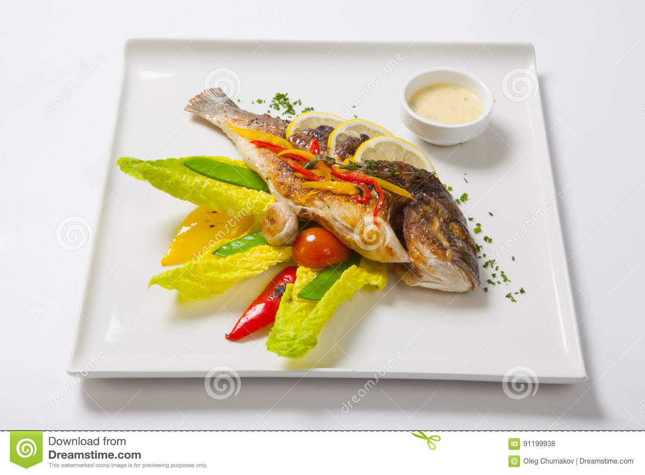 Grilled whole fish decorated with leaves of lettuce and cherry tomato, served with garlic sauce. Fried whole fish