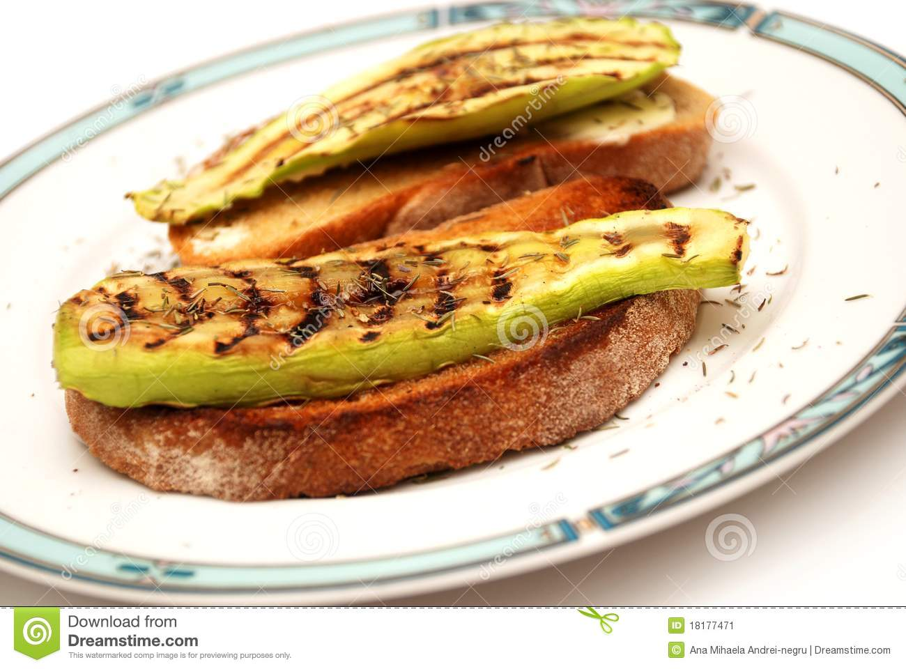 Freshly grilled slices of zucchini with toast bread and butter, on a ...