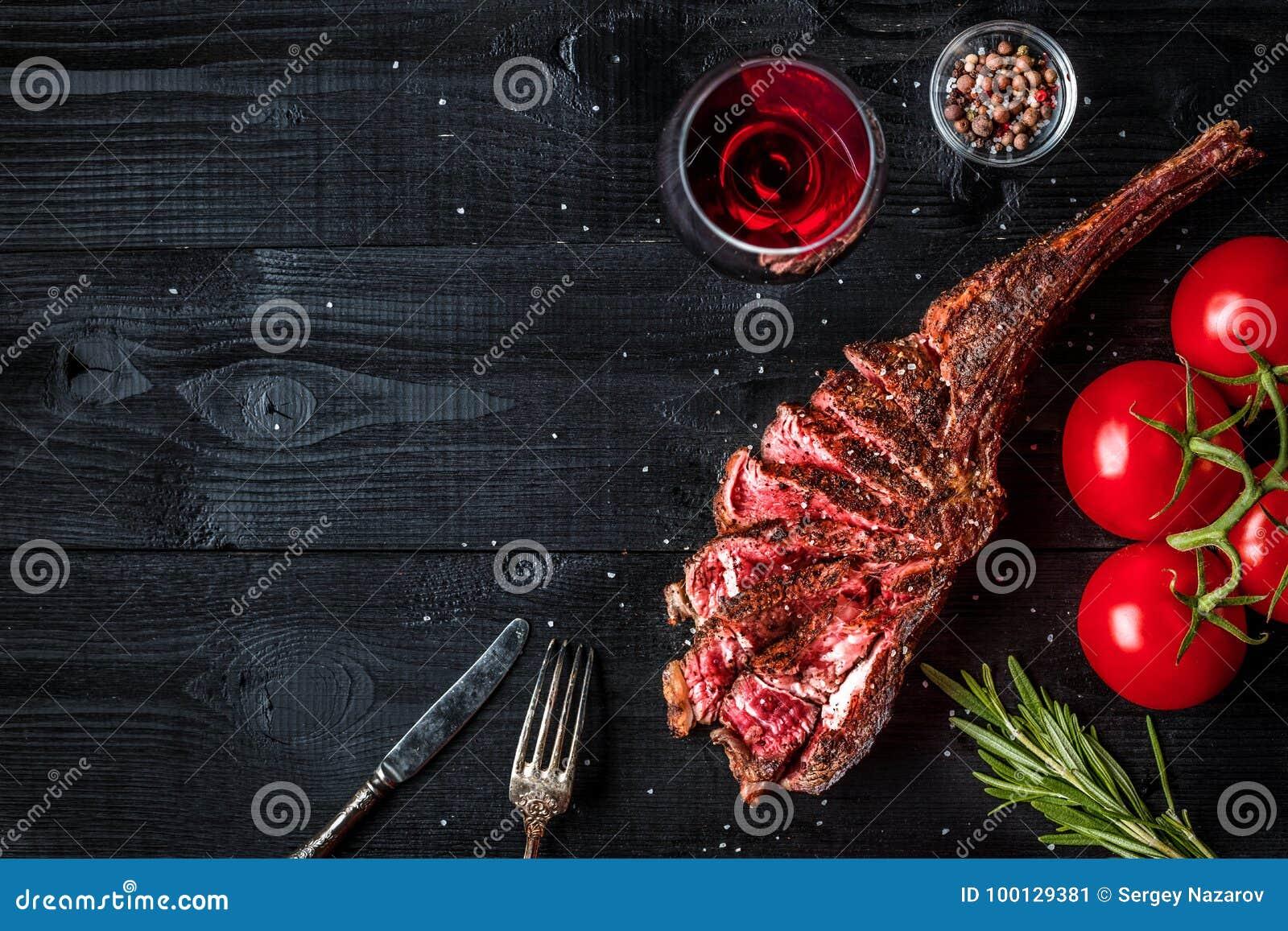 Grillen Sie trockene gealterte Rippe des Rindfleisches mit Gewürz, Gemüse und Glas der Rotweinnahaufnahme auf schwarzem hölzernem