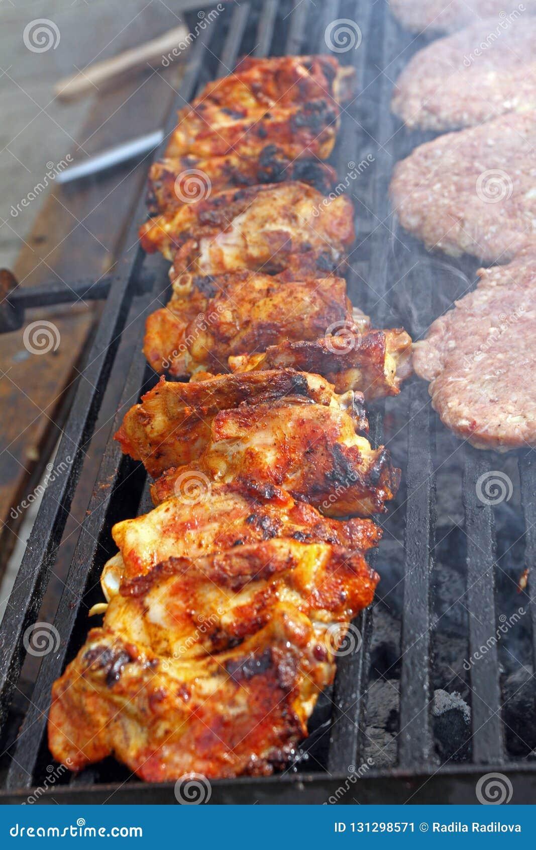 Griller des saucisses, hamburgers, bifteck de porc sur le gril de gaz de barbecues pour la partie Hot-dogs, saucisses et hamburge
