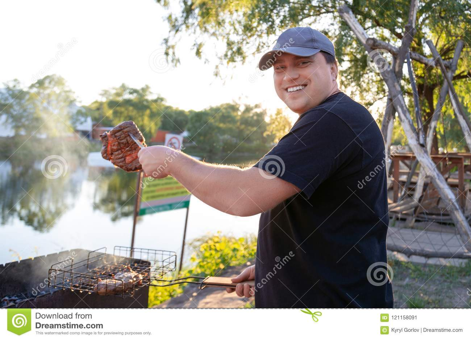 Grillfestparti nära sjön eller floden utomhus Man som grillar köttbeafbiff på öppen brandfyrpanna Sommarsemester och bbq