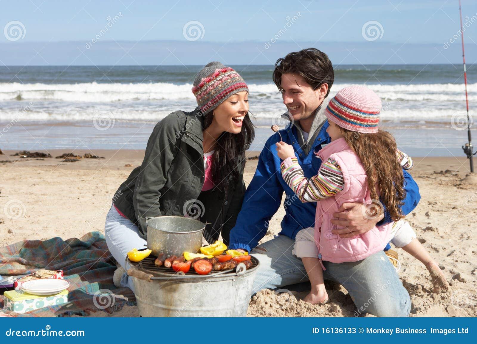 Grillfeststrandfamilj som har vinter