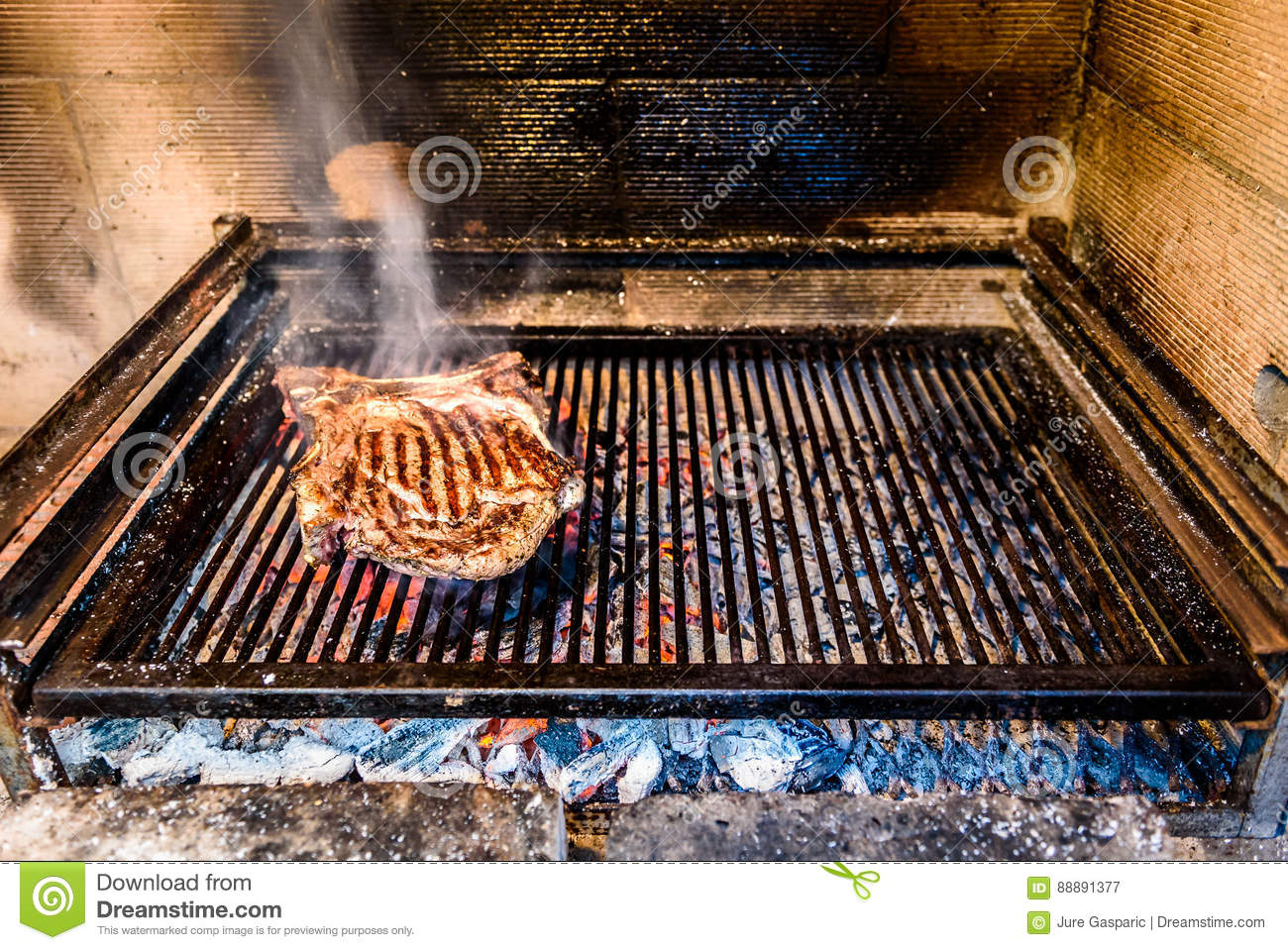 grilling big t bone steak on natural charcoal barbecue grill