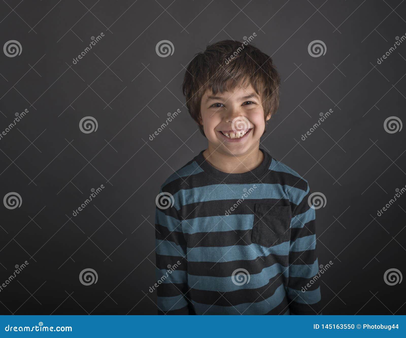 Grimacerie du garçon dans la chemise rayée