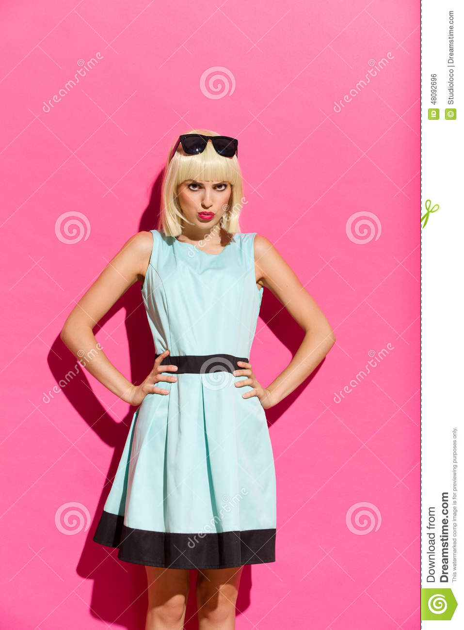 Grimacing blonde girl in light blue dress posing with hands on hip ...