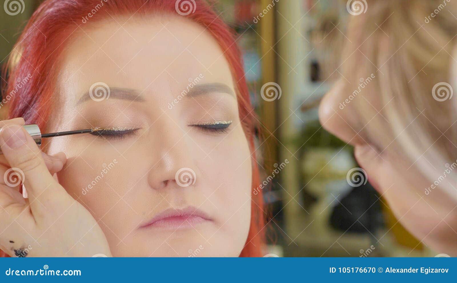 Grimeur die make-up toepassen om het oog van ` te modelleren s Sluit omhoog mening