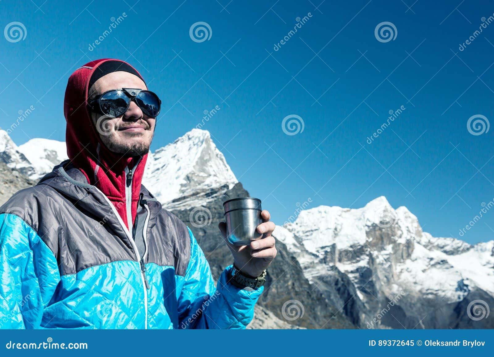 Grimpeur de montagne heureux ayant le rafraîchissement de la tasse thermo