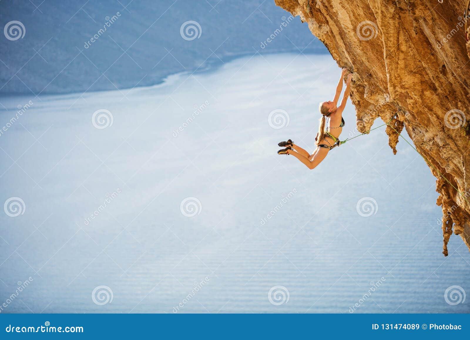 Grimpeur de roche féminin sautant sur des prises sur l itinéraire exaltant sur la falaise