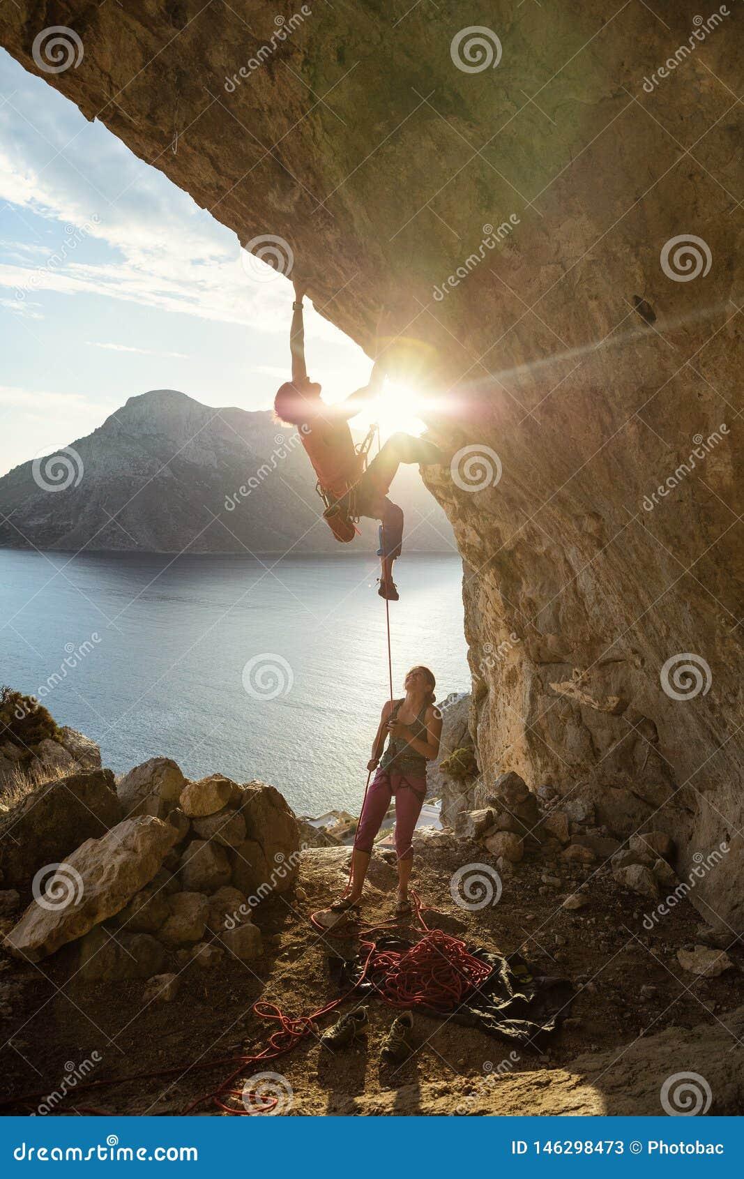 Grimpeur de roche masculin commençant contestant l itinéraire sur la falaise au coucher du soleil, grimpeur féminin l assiégeant