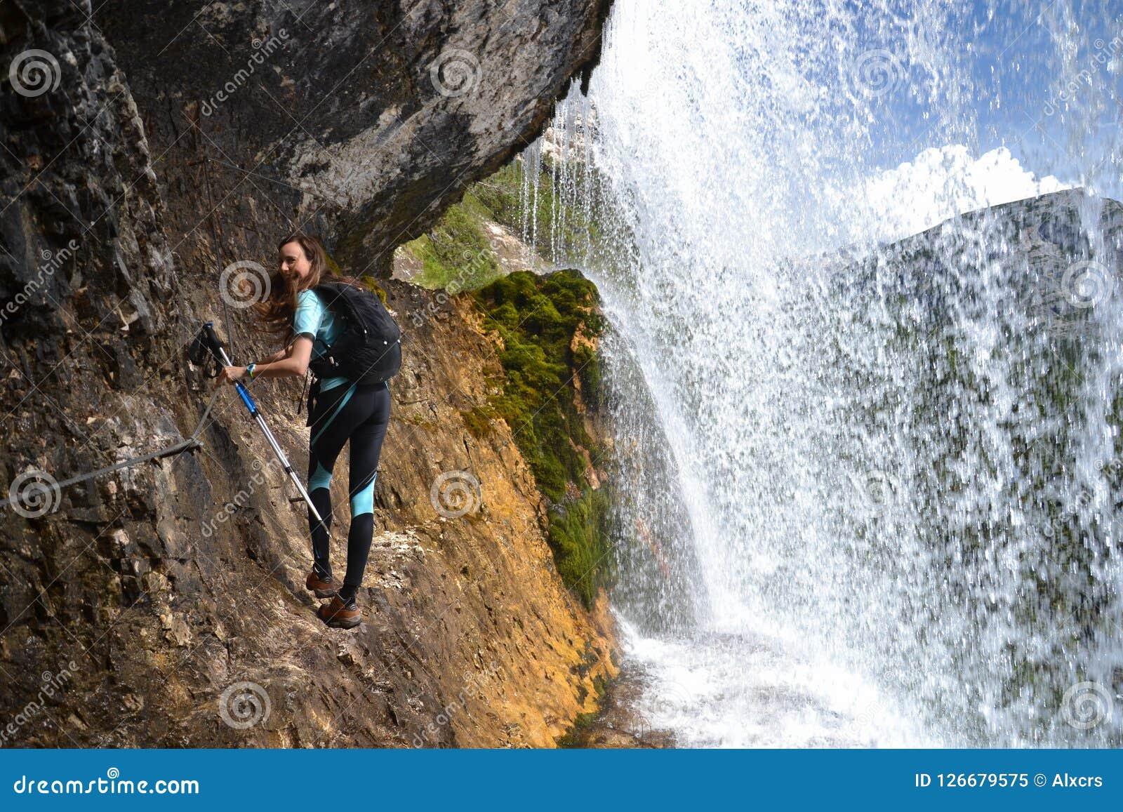 Grimpeuse de femme sur la roche par la cascade
