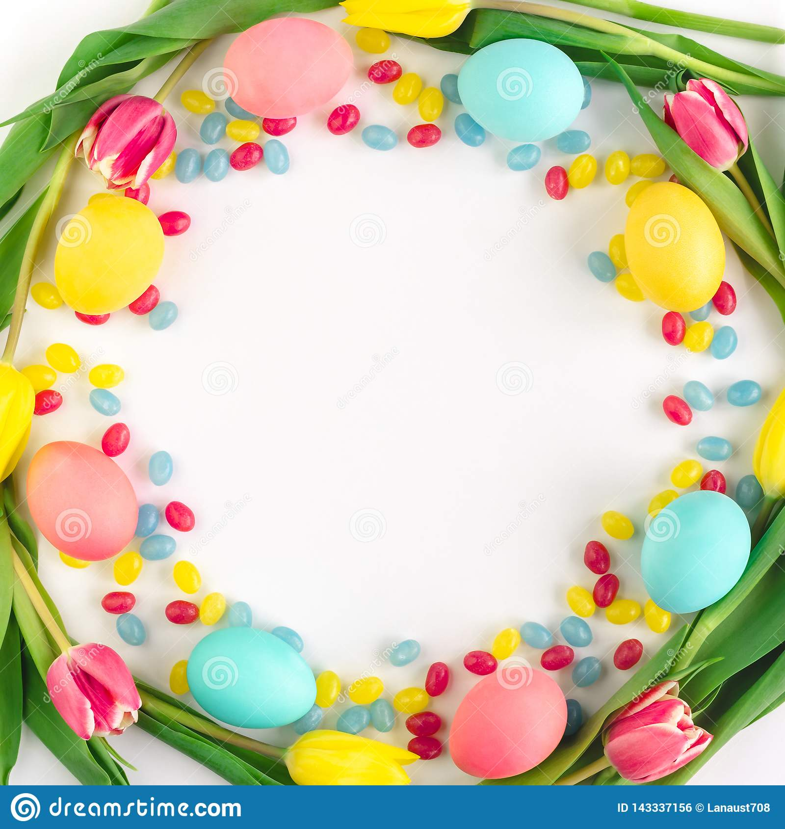 Grinalda da P?scoa feita de tulipas amarelas, de ovos coloridos e de doces no fundo branco Configura??o lisa