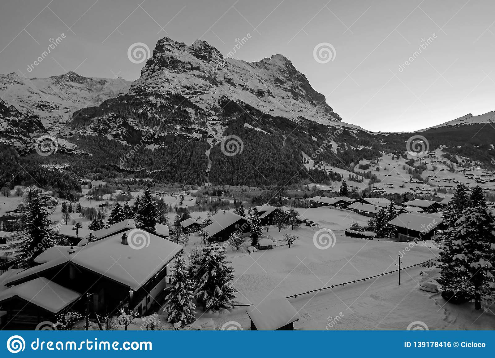 Grindelwald village at dusk with Mt. Eiger peak, snow covered landscape in winter, black white photography, Switzerland