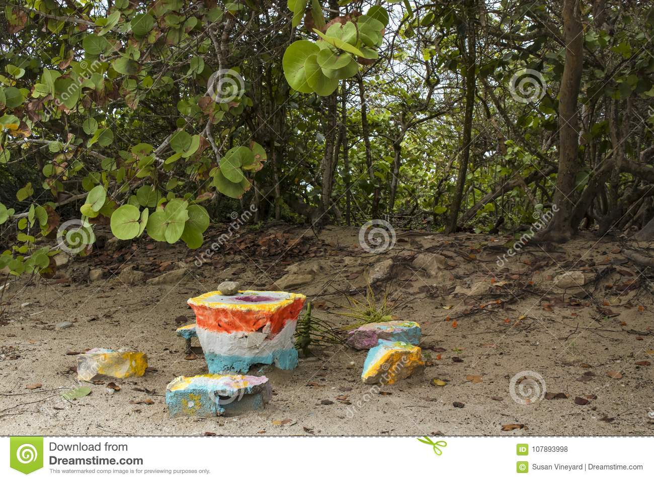 A grinding table with stone grinder made out of brightly painted pieces of concrete and rocks by the beach and tro