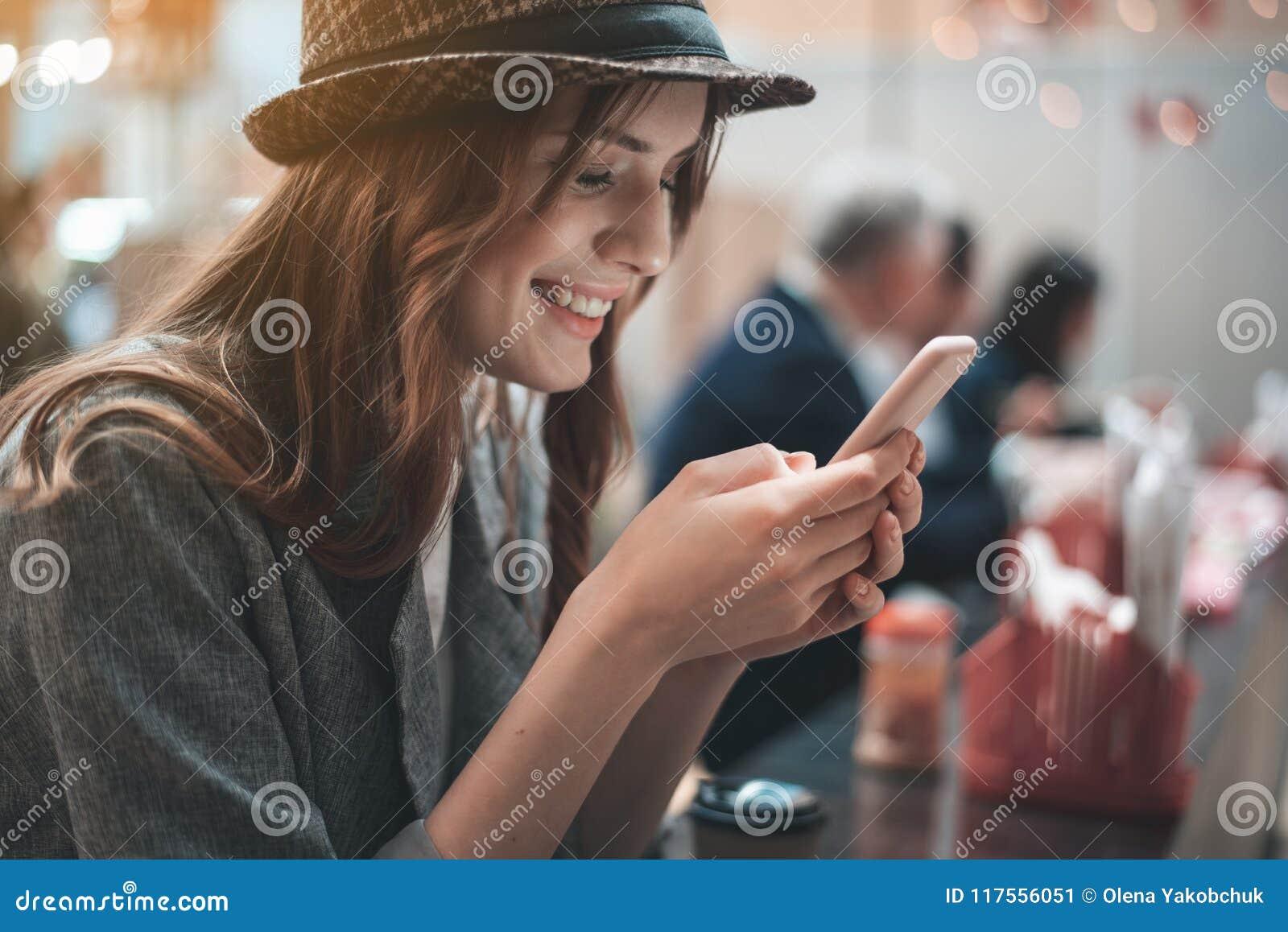 Grinning женщина использует smartphone в кафе
